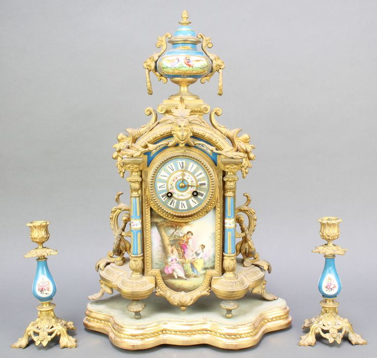 Lot 816, A 19th Century Spelter porcelain 3 piece clock garniture comprising striking mantel clock with Roman numerals contained in a porcelain and gilt spelter case surmounted by a lidded urn (case f) and a pair of matching candlesticks raised on pierced supports (sconces missing), Est £100-200
