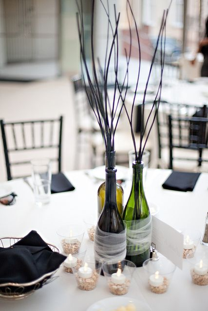 Fun wine bottle centerpiece idea wrapped with tulle and surrounded by candles!  You could use branches with blossoms on them for Spring or substitute flowers in their place, too :)