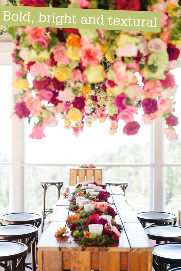 A bright and playful moss and floral runner decorates the bridal table, whilst an insanely gorgeous suspended masterpiece of pink, green and yellow florals hangs above.