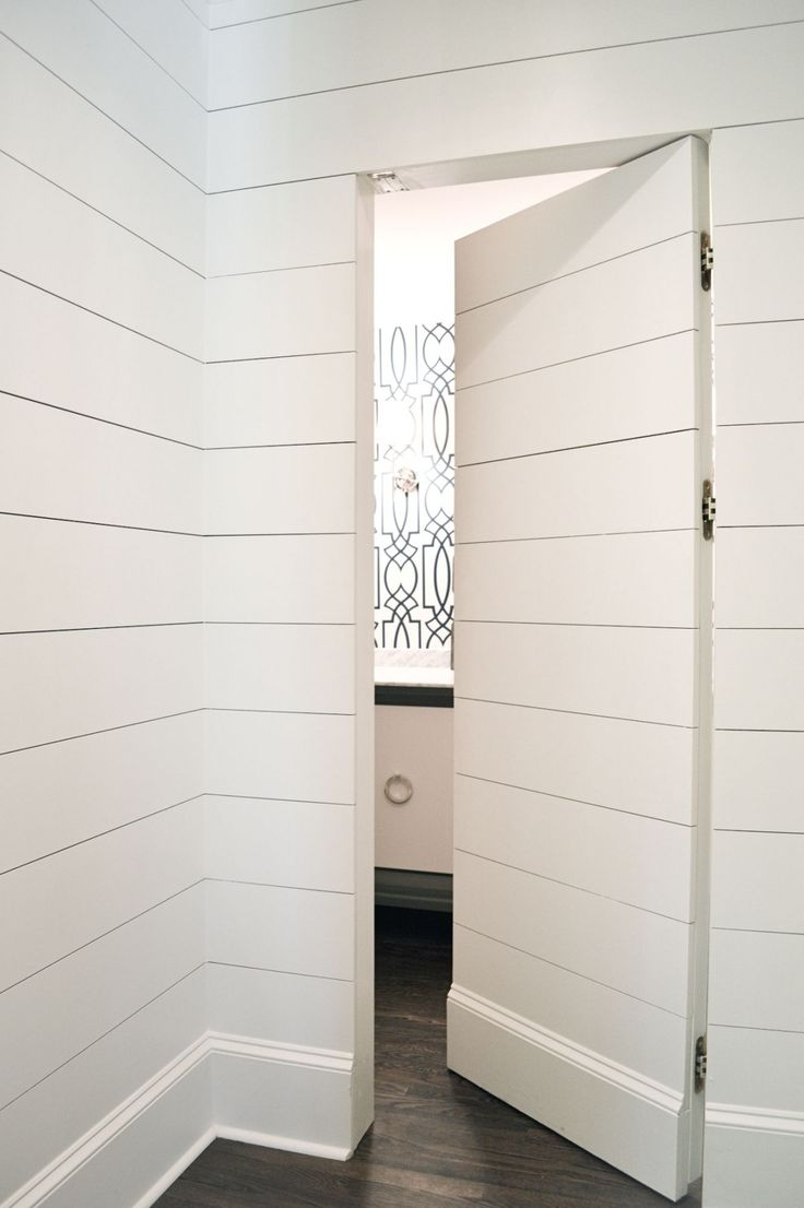 A hall paneled in tongue and groove paneling frames a secret hidden door opening to powder room boasting white floating vanity topped with white marble