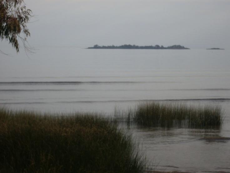 Uno de los islotes frente a la Rambla de Colonia del Sacramento (Departamento de Colonia) parece colgado en un escenario formado por un gris uniforme entre el cielo y el Río de la Plata.