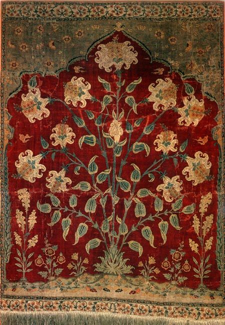Fig. 207, Pg. 384, Prayer Rug, Lahore, 17th Century, wool on silk warps and wefts, 49x36 in. A fine made carpet, possibly a part of a larger carpet with multiple arches. The Floral design comes from European herbals, like before in the Taj Mahal. The design was made strongly under Mughal reign, based on the inclusion of the Chinese rocky landscape at the bottom, and the clouds inserted between the blossoms.