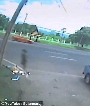 In a chilling scene showing the aftermath of a crash between a truck and a motorbike, a grainy spectre appears to hang in the air above the corpse of a girl caught up in the accident in Thailand.