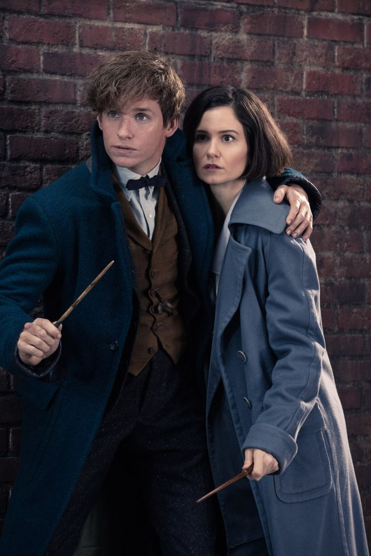 Newt Scamander places his arm round Tina Goldstein as they shelter anxiously with…