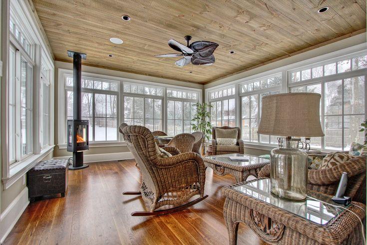 Rustic Sunroom, Antique Wood Floor, Wood Burning Stove, Wicker Furniture, Wood Paneling, Window Wall