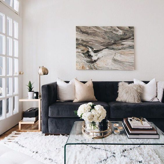 Coordinated colours, dark blue/grey couch, white, beige and generally neutral textiles and rug