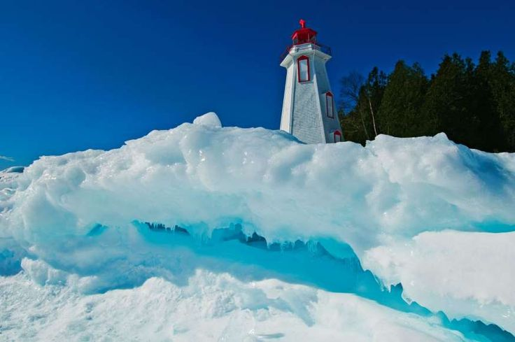 Lighthouse in winter at edge of Georgian Bay in Tobermory, Bruce Peninsula National Park, Ontario, Canada