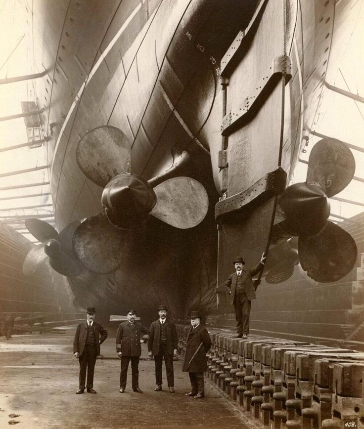 1909. Men stand underneath propellers fitted to RMS Mauretania in Canada Dock in Liverpool.…""