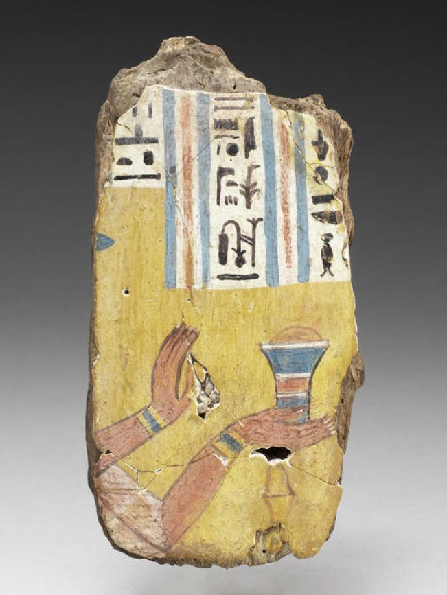 An Egyptian polychrome painted wood coffin fragment  Third Intermediate Period, circa 1069-702 B.C. With the remains of three columns of text above a man's arms outstretched, offering a container with unguent, the central column reading 'Amen-Re King of the Gods, scribe of..', the last column with '..hotep', 6in (15.1cm) high, mounted