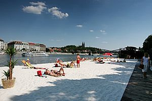 Beach consists of 200 m long sandy area equipped with deck chairs, umbrellas, showers, changing rooms, facilities for summer sports, a stage for cultural events and a pier for yachts and boats.