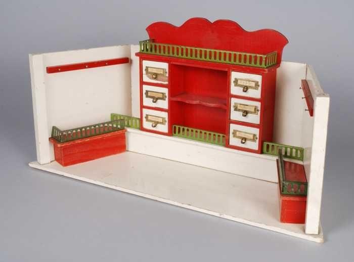 Miniatuur kruidenierswinkel met leg- en ladenkast tegen achterwand, witte wanden, kast rood met groen metalen hekwerk - Museum Rotterdam