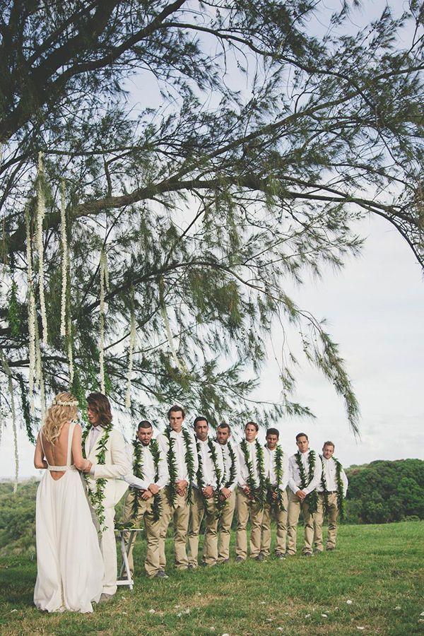 Groomsmen at a Hawaiian wedding wearing maile leis, white shirts and khaki pants.