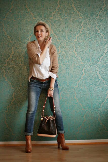 classic style: casual jeans with heeled boots and tucked in button-up with neutral sweater