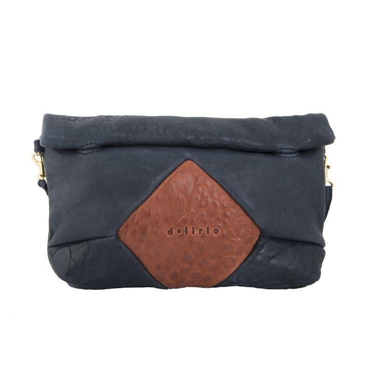El bolso Rhombus azul marino tiene un rombo marrón en el centro, El cierre es de imanes, sin cremallera. El forro interior es de algodón, gris claro y contiene un bolsillo con cremallera.