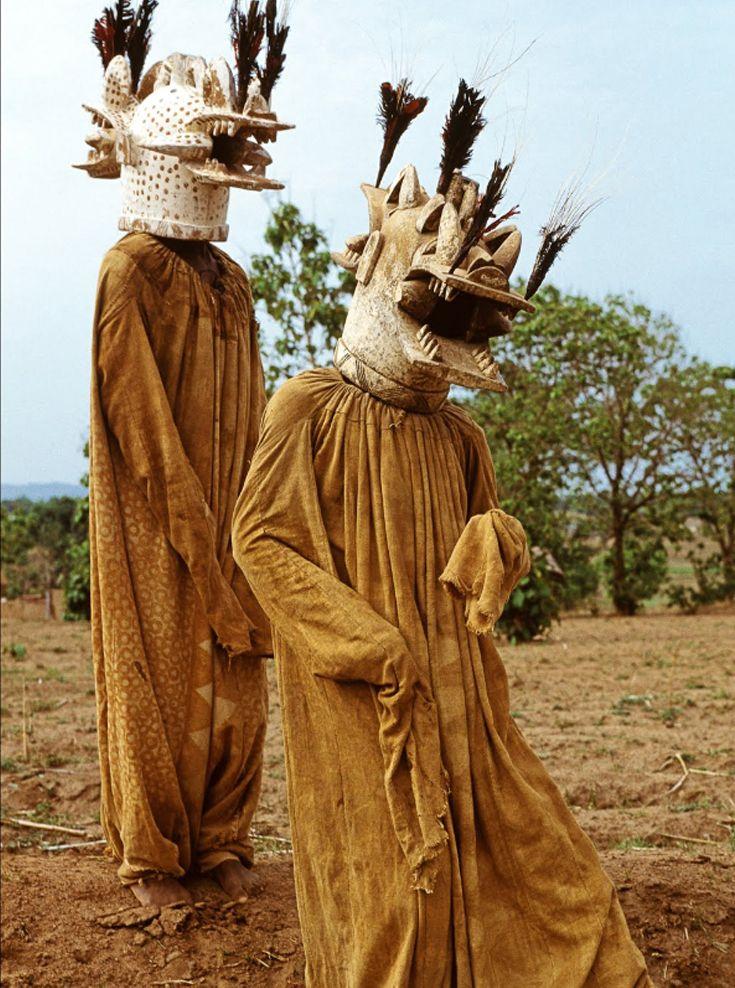 África | Dois membros da tribo Senufo Wambele utilizando trajes que são usados durante rituais de funeral. Costa do Marfim. | Fotografia de: Carol Beckwith & Angela Fisher. Datado de: 1994.