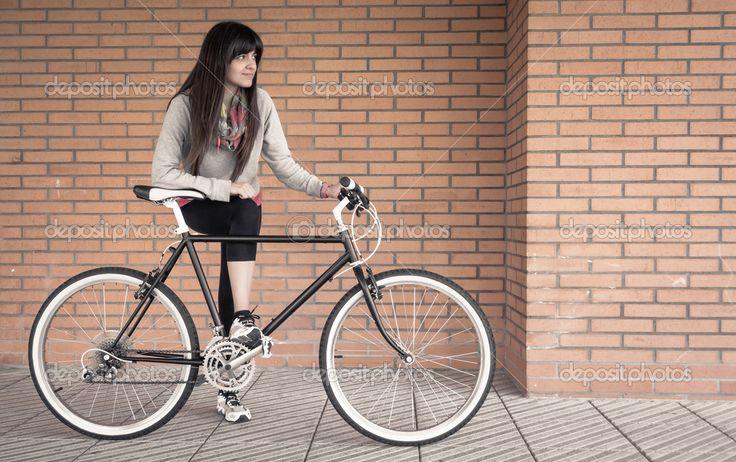 Downloaden - Mooie jonge sportieve vrouw poseren met aangepaste fixie fiets over een oranje muur op de achtergrond — Stockbeeld #46656271