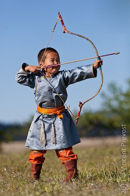 """Young Mongolian archer at Nadaam festival in Tsagaannuur, Mongolia. Naadam is properly know as """"Eryn gurvan naadam,"""" after the three manly games of wrestling, horse racing, and archery making up the core activities of the National Festival. It is the most important festival of the year."""