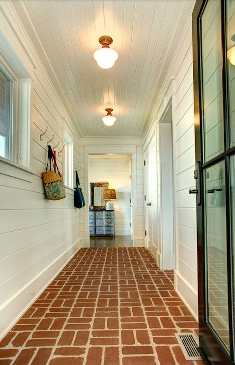 Stunning mudroom features a black glass door opening to for Beach house flooring ideas