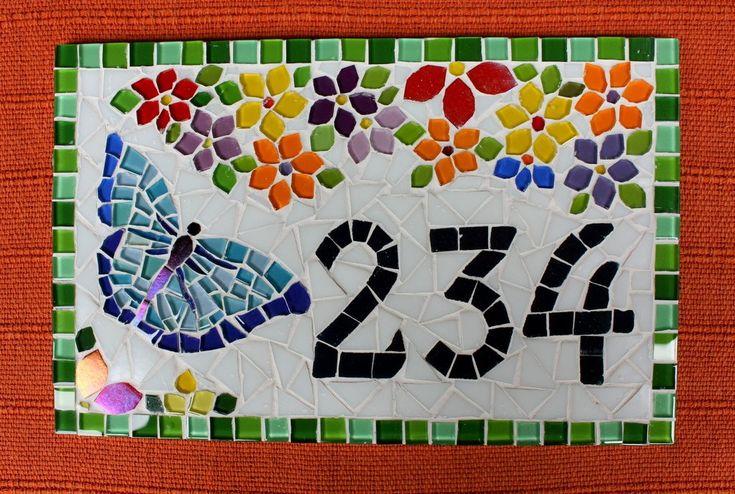 As flores coloridas sempre nos remetem a momentos alegres, a boas energias. E quando vemos uma borboleta então, um sentimento de felicidade e de leveza nos invade! Essa placa com número residencial é feita em base cimentícia, com colas e argamassas especiais para áreas externas . O mosaico é com pastilhas de vidro, azulejos especiais e pastilhas cristal.