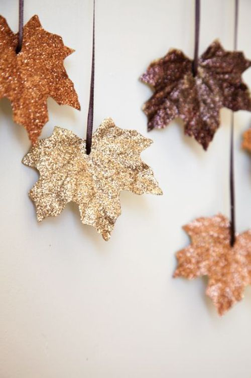 Melt candle wax into a pan and drop the leaves in. When both sides are covered, dip them in glitter and then hang them up by ribbons to dry.