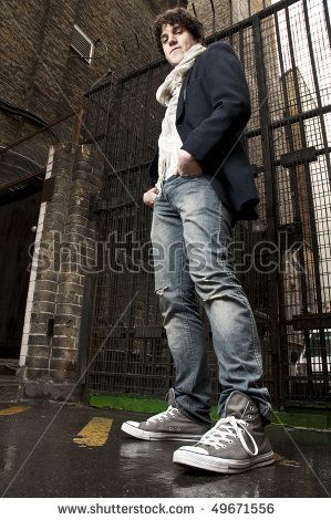 stock photo : Low angle portrait of young man looking down with gate in the background.