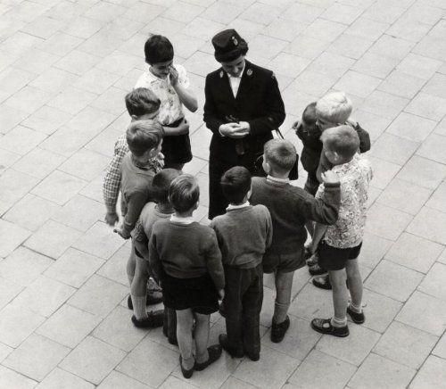 Kinderpolitie, kinderbescherming, Nederland. Een agente van de kinderpolitie wordt omringd door een groepje kinderen [vermoedelijk op een schoolplein]. Zonder plaats of datum [1962]. Foto uit een reportage over 'Politiemensen zonder knuppel'.