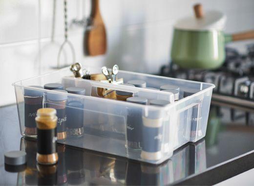 Foto eines transparenten IKEA SAMLA Einsatzes für Box mit Gefäßen voller Kräuter und Gewürze auf einer Arbeitsplatte