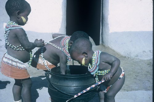Africa | Xhosa kiddies at a food pot. Eastern Cape - Transkei. South Africa. | Lister Haig Hunter.