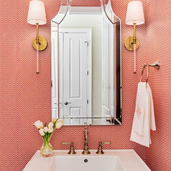 Fun and vibrant powder bath featuring brass sconces, coral geometric wallpaper, and a detailed mirror.