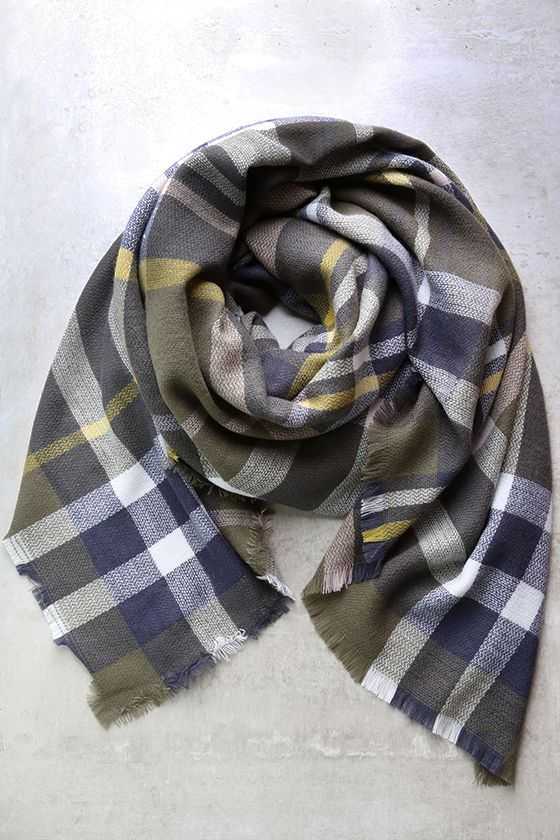 "Grab the Meet Me at the Oak Tree Olive Green Plaid Scarf and join us for a picnic! Soft, woven fabric boasts a classic plaid pattern in shades of olive green, blue, white, pink, and yellow as it shapes a cozy, blanket scarf with fringe hems. Scarf measures 57"" wide and 59"" long. $18"