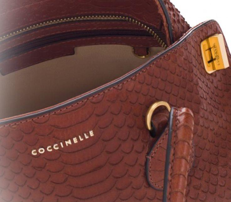 La borsa a mano Dafne della Coccinelle è prodotta in pelle e presenta, sui lati, chiusure in metallo che le conferiscono un movimento di forte tendenza. La vestizione in pelle è ad effetto pitone.