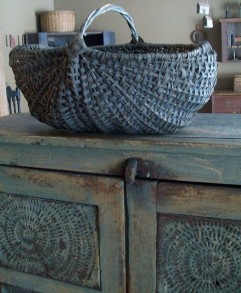 A LARGE GATHERING BASKET WITH A TWISTED HANDLE.