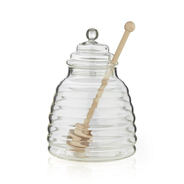 This adorable glass beehive is purposeful about storing and dispensing honey with the accompanying unfinished wood dipper. Natural beehive shape is realized in industrial-strength clear borosilicate glass with a ringed dipper designed for controlled drizzling.