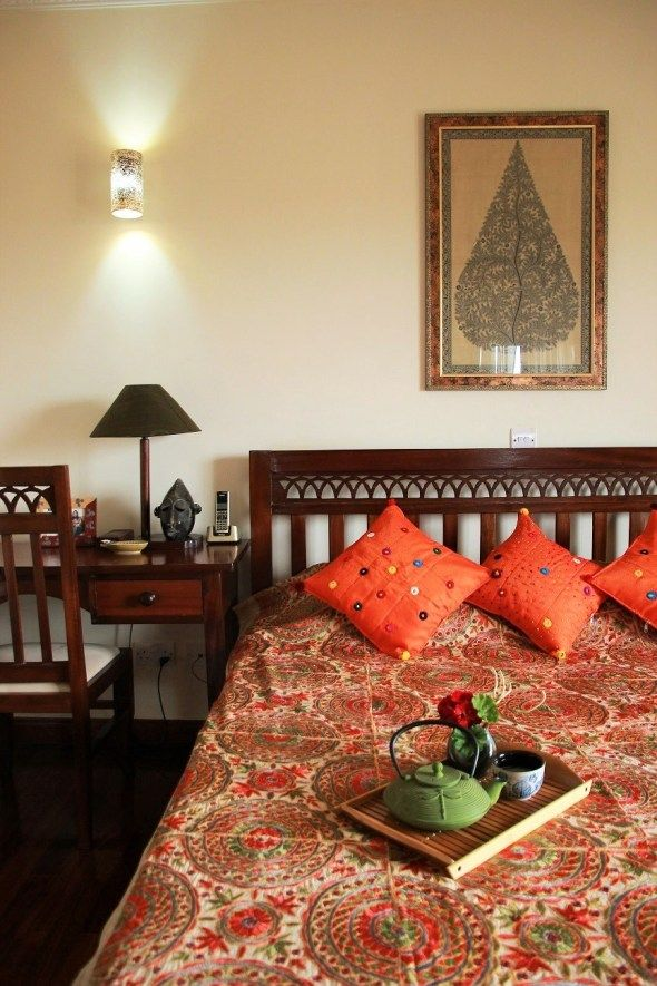 Orange bed linens. Framed pictures. Home Tour: Hemal Paliwal's Lotus-themed home in Kenya. | The Keybunch Decor Blog. |