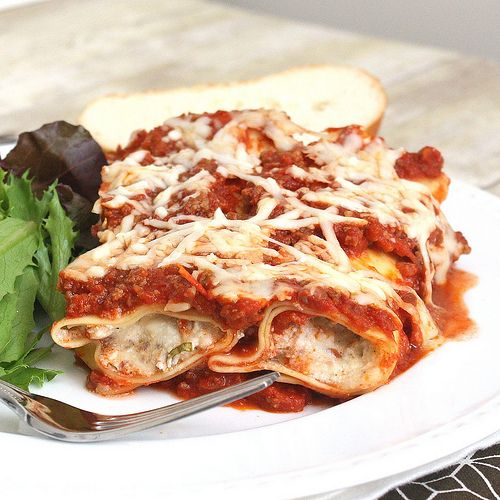 Baked Manicotti with Meat Sauce~ Cheesy, meaty filling stuffed inside of pasta noodles and topped with a rich, meaty sauce and more cheese! If you scan the ingredient list you'll notice there's pepperoni in the meat sauce,