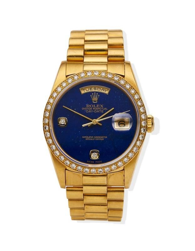 A Gentleman's gold President Day Date wristwatch, Rolex, circa 1995. Automatic. 36mm. Ref: 18348. Cal. 3155. Serial number W633210. Lapiz Lazuli dial with applied diamond set numerals at 6 and 9. Centre sweep seconds, day aperture at 12 o'clock and date aperture at 3 o'clock.Case, dial, and movement signed.Original President bracelet numbered 8385. Box, outer box, papers, two extra links and tag. - Price Estimate: $19000 - $26000