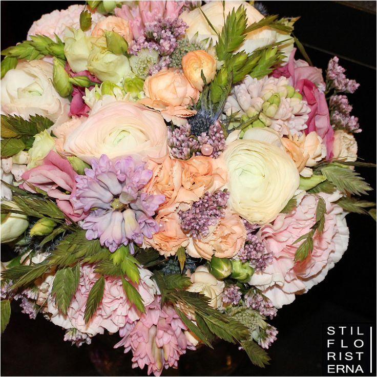 Romantisk vårbrudbukett i kompakt handbunden form, i ljusa aprikosa, rosa och lila toner, med bland annat ranunkel och hyacinter.