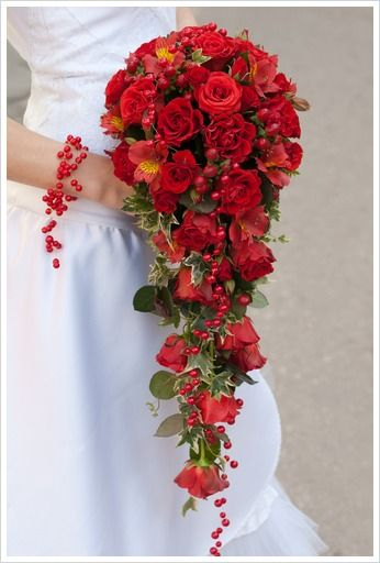 Red Cascade  Here is a cascading bouquet of red roses, red carnations and red alstromerias, with english ivy and red beads trickling down the bouquet. The bride also wore a wrist bracelet made of the same red beads.