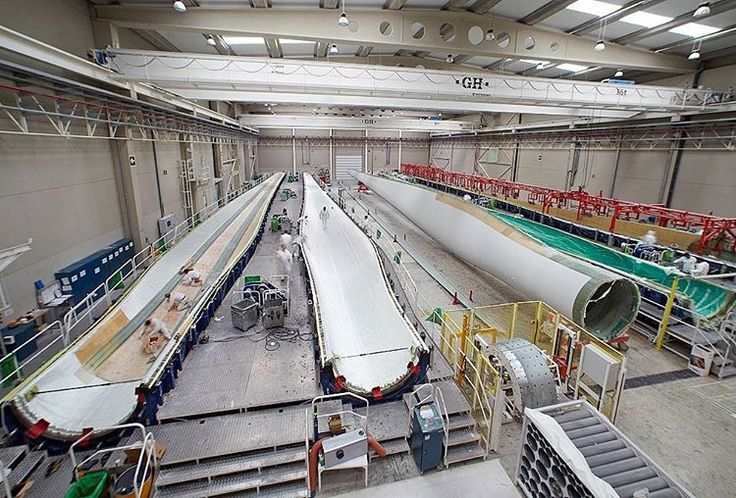 ACCIONA Blades' employees, an affiliate of ACCIONA, building these giants wind turbine blades at Lumbier's plant, in Navarre, Spain. The plant manufactures blades of up to 64.7 metres with a 132-metre rotor.