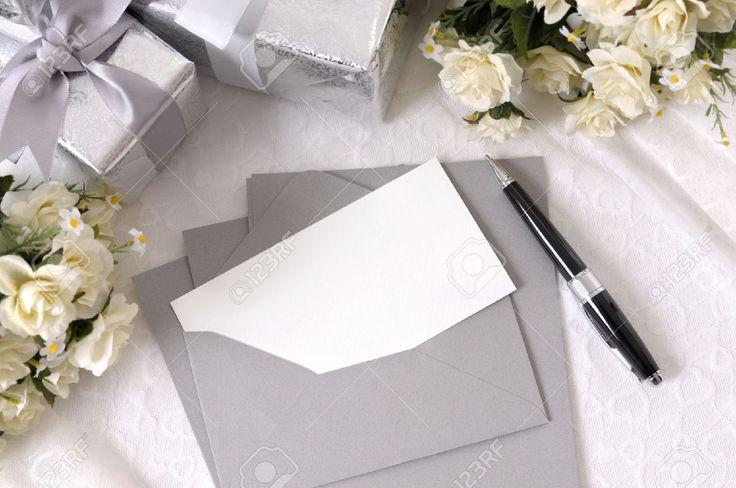 Foto de archivo - Papel de escribir o invitación de la boda con el sobre establecidas en cordón nupcial con varios regalos de boda y ramos de rosas blancas.