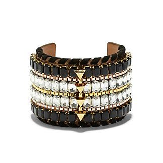 """Embellished Wide Cuff-This bracelet is calling your name, and we have to agree you two would make a perfect pair! This tiered cuff has a lot going on, but we say """"the more the merrier""""! Glimmer in pronged crystals, chain-like slivers of gold and rosegold, leather ribbon and a series of 3D arrows. Let it captivate with a solid black dress."""