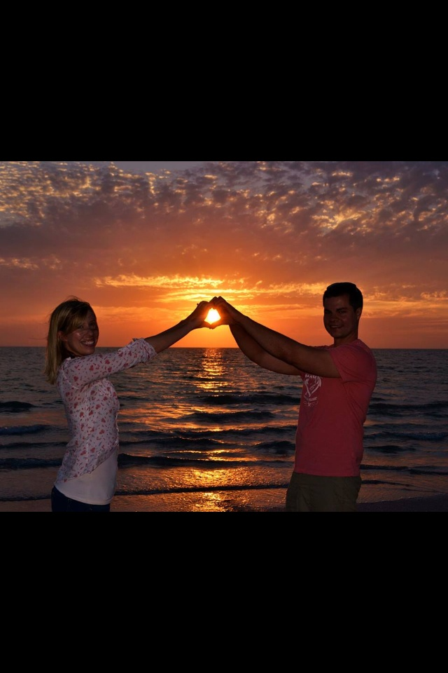 First anniversary picture on the beach at sunset, holding hands, love, heart, hold the sun, marriage
