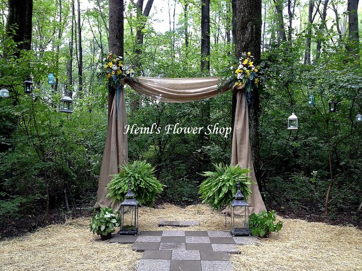 Outdoor wedding arch or burlap with flowers and boston ferns. Daisies and lilies decorate the arch's corners.