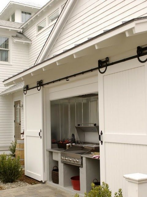 Built in Grill carriage house sliding doors. ( What a great way to keep an outdoor kitchen out of the elements!)