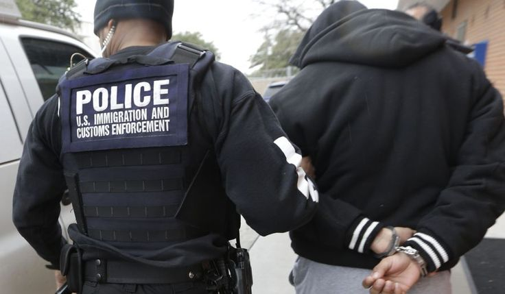 A U.S. Immigration and Customs Enforcement agent escorts a handcuffed undocumented immigrant convicted of a felony that was taken into custody during an operation in Dallas on March 6, 2015. (Associated Press) **FILE**