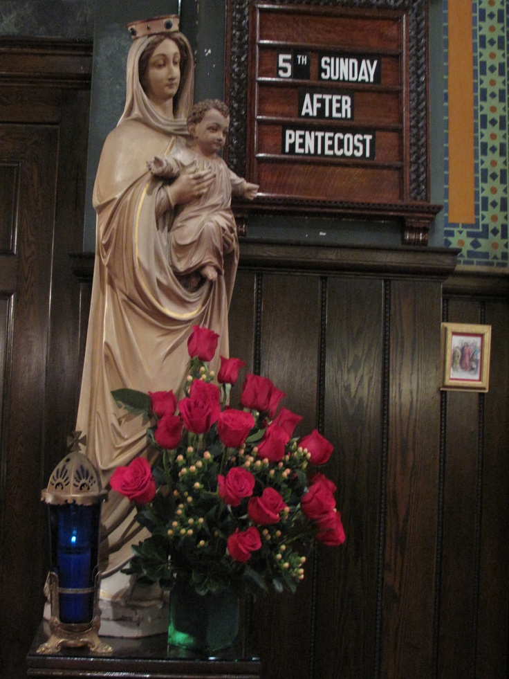 Roses adorn the statue of Mary holding the infant Jesus.
