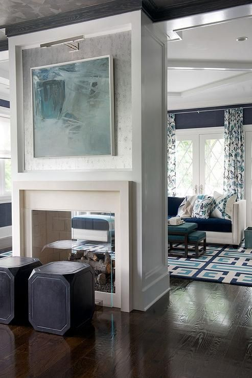 An open floor plan boasts a double sided fireplace with clear see through firebox under a blue abstract art piece illuminated by a picture light separating the living room from the dining room.