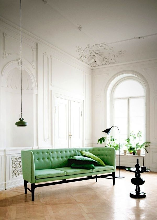 mid century design with pop of color. green couch. wall moulding. 1920's couch.