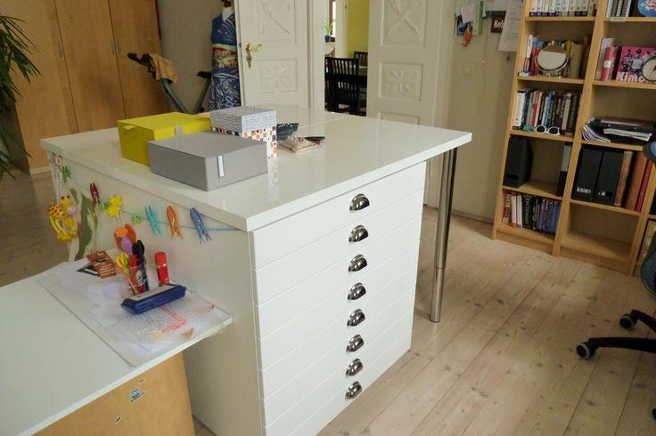 Die Schubladenelemente sind eigentlich Küchenunterschränke mit 10 Zentimmeter hohen Schubladen (8 Stück). Zwei Stück davon an der Rückseite zusammen gebaut und mit zwei Tischplatten bestückt macht 1,20 Meter im Quadrat.