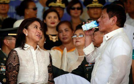 Vice President Leni Robredo watches Philippines President Rodrigo Duterte drinking coconut juice after a military parade at main military Camp Aguinaldo in Quezon city Metro Manila